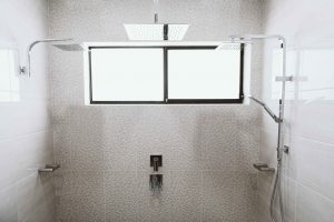 Three rainfall showers add drama to this bathroom